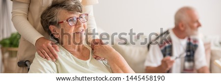 Panoramic view of elderly lady on wheelchair holding hands with supporting volunteer standing behind her