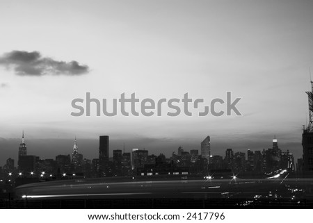 panoramic view of elevated subway lines and Manhattan skyline through the passing train in the early winter evening in black and white