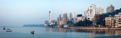 Panoramic view of elite Walkeshwar stretch of South Mumbai along Arabian Sea bathed in morning sun. Small country fishing crafts are seen bobbing in the sea. Copy space