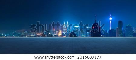 Panoramic view of empty concrete tiles floor with city skyline. Night scene.