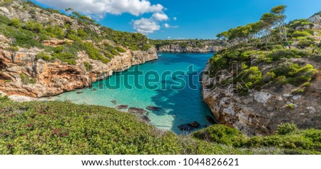 Panoramic view of Es calo des Moro beautiful beach. Pine tree shadows on crystalline water. Classified as one of the best beaches in the world. Located in Santanyi, Majorca, Balearic Islands, Spain