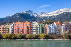 Panoramic view of famous colourful houses and snow-capped alpine mountain tops in the background in the historic city center of scenic Innsbruck on a beautiful sunny day with blue sky, Tyrol, Austria