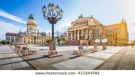 Panoramic view of famous Gendarmenmarkt square with Berlin Concert Hall and German Cathedral in golden evening light at sunset with blue sky and clouds in summer, Berlin Mitte district, Germany #411844984