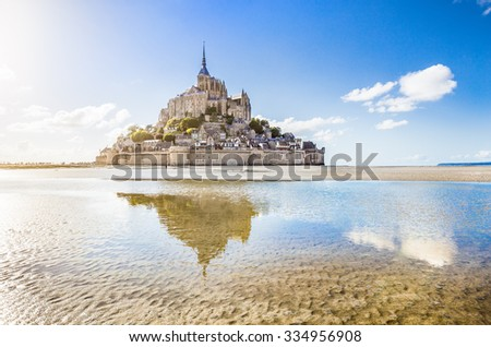 Stock Photo Panoramic view of famous historic Le Mont Saint-Michel tidal island on a sunny day with blue sky and clouds in summer, Normandy, northern France