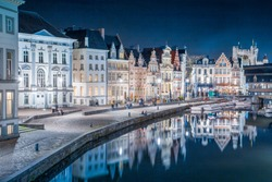 Panoramic view of famous Korenlei in the historic city center of Ghent illuminated in beautiful post sunset twilight during blue hour at dusk with Leie river, Ghent, East Flanders, Belgium
