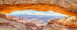 Panoramic view of famous Mesa Arch, iconic symbol of the American West, illuminated golden in beautiful morning light on a sunny day with blue sky and clouds, Canyonlands National Park, Utah, USA