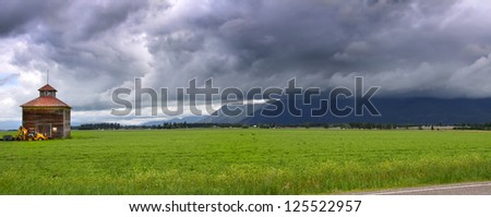 Panoramic view of farm landscape and stormy weather - stock photo