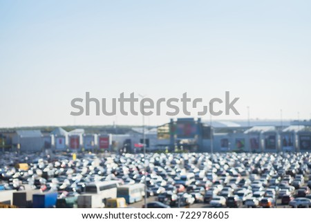 Panoramic view of Full car park next to shopping center outside. Cars on large parking lots, traffic jams and crowded outdoor parking. Abstract blurred background
