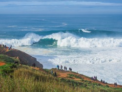 Panoramic view of gigantic powerful foamy waves in North Beach of Nazaré or Silver Coast, phenomenal underwater canyon, continental shelf, popular surf route in Europe, Portugal. Stormy Atlantic ocean
