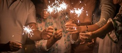 panoramic view of group of friends mixed ages celebrate together in the night with sparklers light. new year eve or birthday or christmas event to live friendship and family with happiness