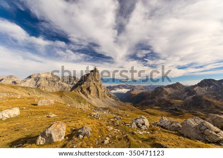Panoramic view of high mountain range in a colorful autumn with green yellow meadows and rocky mountain peaks. Wide angle shot in the Italian French Alps.