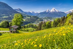 Panoramic view of idyllic mountain landscape in the Alps with fresh green mountain pastures with flowers and old traditional mountain lodge in springtime