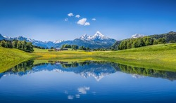 Panoramic view of idyllic summer landscape in the Alps with clear mountain lake and fresh green mountain pastures in the background