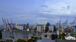 Panoramic view of industrial port and container loaders. Port landscape with shore cranes and grain elevators under clouds floating in blue sky