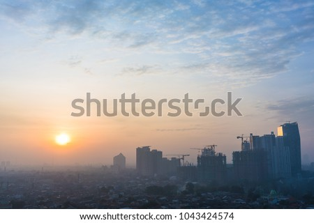 Panoramic view of Jakarta cityscape with skyscrapers and buildings under construction at sunrise
