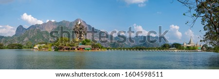 Panoramic view of Kyauk Kalap Monastery in the middle of an artificial lake, which is connected to the mainland by a bridge. Stock fotó ©