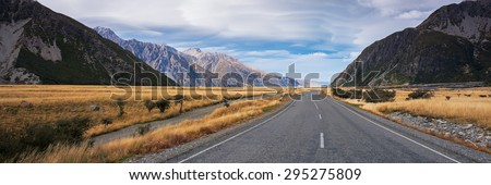 Panoramic view of long road to Mount Cook, New Zealand during autumn season. Leading line, empty road. Not centered.
