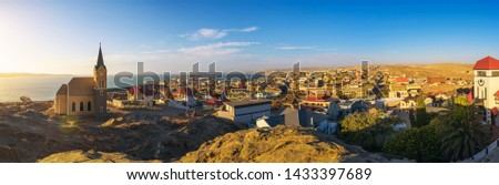 Panoramic view of Luderitz in Namibia at sunset with lutheran church called Felsenkirche and atlantic ocean in the background.