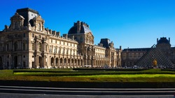 Panoramic view of main courtyard of Louvre Palace with pyramid on sunny autumn day