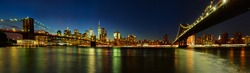 Panoramic view of Manhattan and Brooklyn Bridges from Brooklyn at night. Cityscape of New York