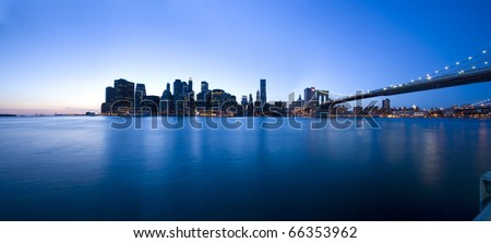 panoramic view of Manhattan skyline and Brooklyn Bridge at dusk over Hudson River with skyscrapers