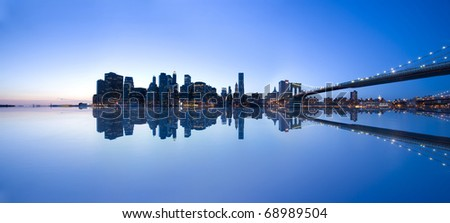panoramic view of Manhattan skyline and Brooklyn Bridge with reflection