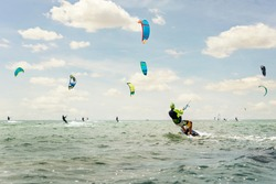 Panoramic view of many people enjoy riding kite surf board in sun uv protection suit on bright sunny day at sea or ocean shore kitesurfing camp spot. Watersport adrenaline fun adventure acitivity
