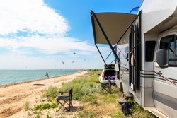 Panoramic view of many surf board kite riders on sand beach watersport spot on bright sunny day against rv camper van vehicle at sea ocean coast at surfing camp. Fun adventure travel sport acitivity