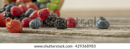 Panoramic view of mixed berry fruits scattered on a textured rustic wooden desk. #429368983