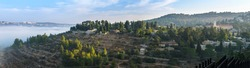 Panoramic view of morning mist and green Judean hills around Ein Kerem neighborhood - biblical birth place of John the Baptist, with Catholic Church of Saint John the Baptist; Jerusalem Israel
