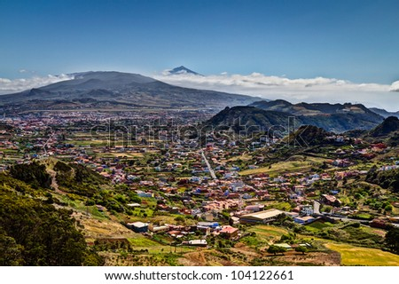 Panoramic view of Mount Teide with many colorful houses in the foreground. Tenerife, Spain