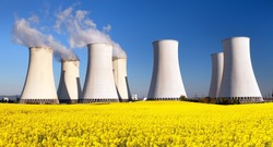 Panoramic view of Nuclear power plant Jaslovske Bohunice with golden flowering field of rapeseed - Slovakia - two possibility for production of electric energy