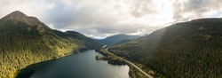 Panoramic View of Peaceful Lake alongside Scenic Road, surrounded by Mountains in Canadian Nature. Aerial Drone Shot. Taken near Stewart-Cassiar Highway, Northern British Columbia, Canada.
