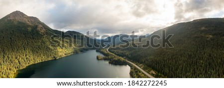 Panoramic View of Peaceful Lake alongside Scenic Road, surrounded by Mountains in Canadian Nature. Aerial Drone Shot. Taken near Stewart-Cassiar Highway, Northern British Columbia, Canada. Foto stock ©