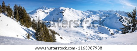 Panoramic view of Portes du Soleil, Alpes. Winter landscape in sunny day with low clouds.