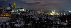 panoramic view of Prague Castle and St. Vitus Cathedral and a snow-covered park in PodveČer in the center of Prague
