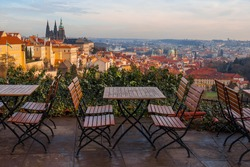 panoramic view of Prague with street cafe chairs on a terrace in the foreground
