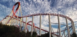 Panoramic view of red roller coaster track with beautiful cloudy sky