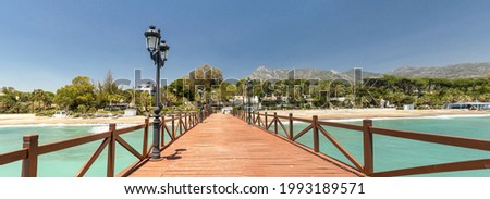 Panoramic view of red wood bridge 'Embarcadero' in Marbella. View of Luxury area Puente Romano, expensive urbanisations. Mountain 'La Concha'. Spectacular travel destination. Emerald water, no people Foto stock ©