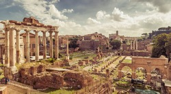 Panoramic view of Roman Forum in summer, Rome, Italy. Roman Forum is remains of famous Roman Empire. Scenery of ancient ruins in Roma city center on sunny day. Vintage style photo of Rome cityscape.