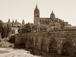 Panoramic view of Salamanca. Pedestrian bridge Puente Romano and famous old town with ancient buildings. Old and new Cathedral of Salamanca, baroque cupola and tall bell tower. Sepia tone photography.