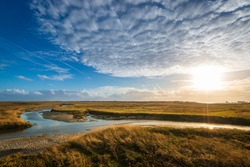 Panoramic view of salt marshes (salt meadows) at north sea coast in Sankt Peter-Ording at sunset against sky