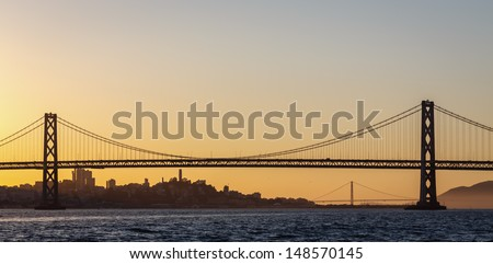 Panoramic view of San Francisco's Bay Bridge  and Golden Gate bridge at sunset with blue, orange and golden sky