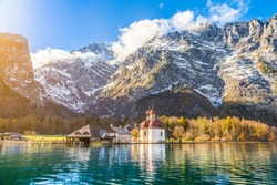 Panoramic view of scenic mountain scenery with Lake Konigssee with famous Sankt Bartholomae pilgrimage church in golden evening light in fall, national park Berchtesgadener Land, Bavaria, Germany