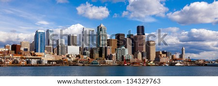 Panoramic view of Seattle waterfront and downtown buildings on a bright day with sun and clouds