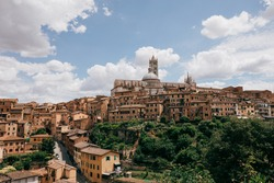 Panoramic view of Siena city with historic buildings and far away Siena Cathedral (Duomo di Siena). Summer sunny day and dramatic blue sky