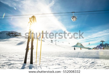 Panoramic view of ski resort glacier and chair lift in french alps - Vacation and travel concept - Winter high season opening with people having fun on mountain - Focus on sport equipment #552008332
