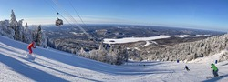 Panoramic view of skiers on Mont Tremblant slopes with aerial gondolas on the background in Quebec, Canada