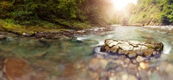 Panoramic view of Sochi river in mountains nearer to the river head, lens flares