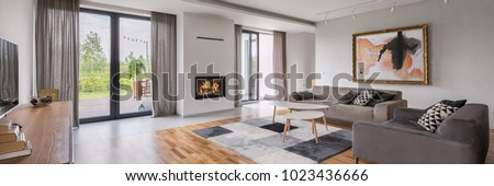 Panoramic view of spacious living room with floor panels, sofa and armchair